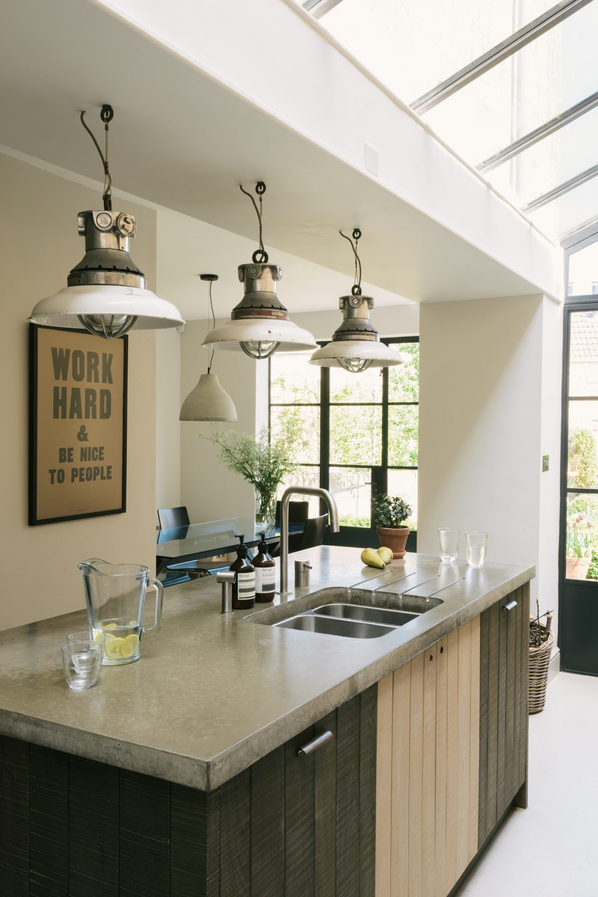Three industrial pendant lights hang above the lovely island.