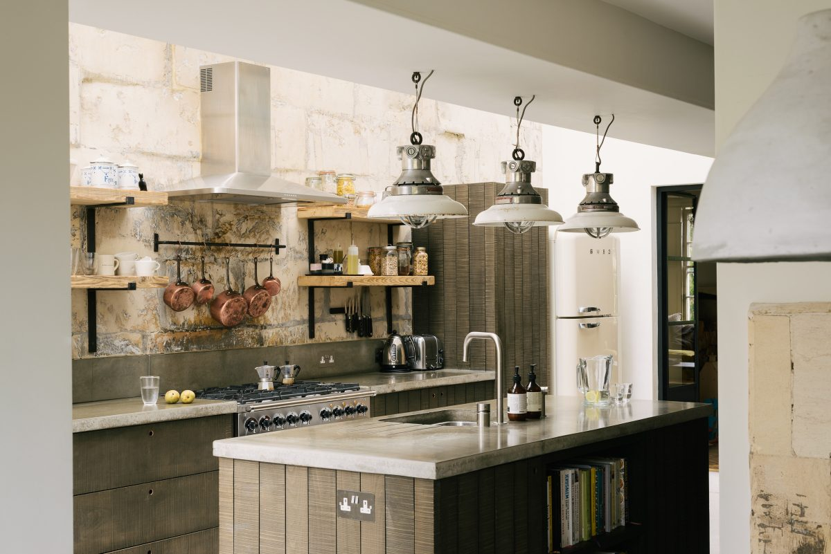 Industrial lights, bare brick walls, copper pans and concrete worktops