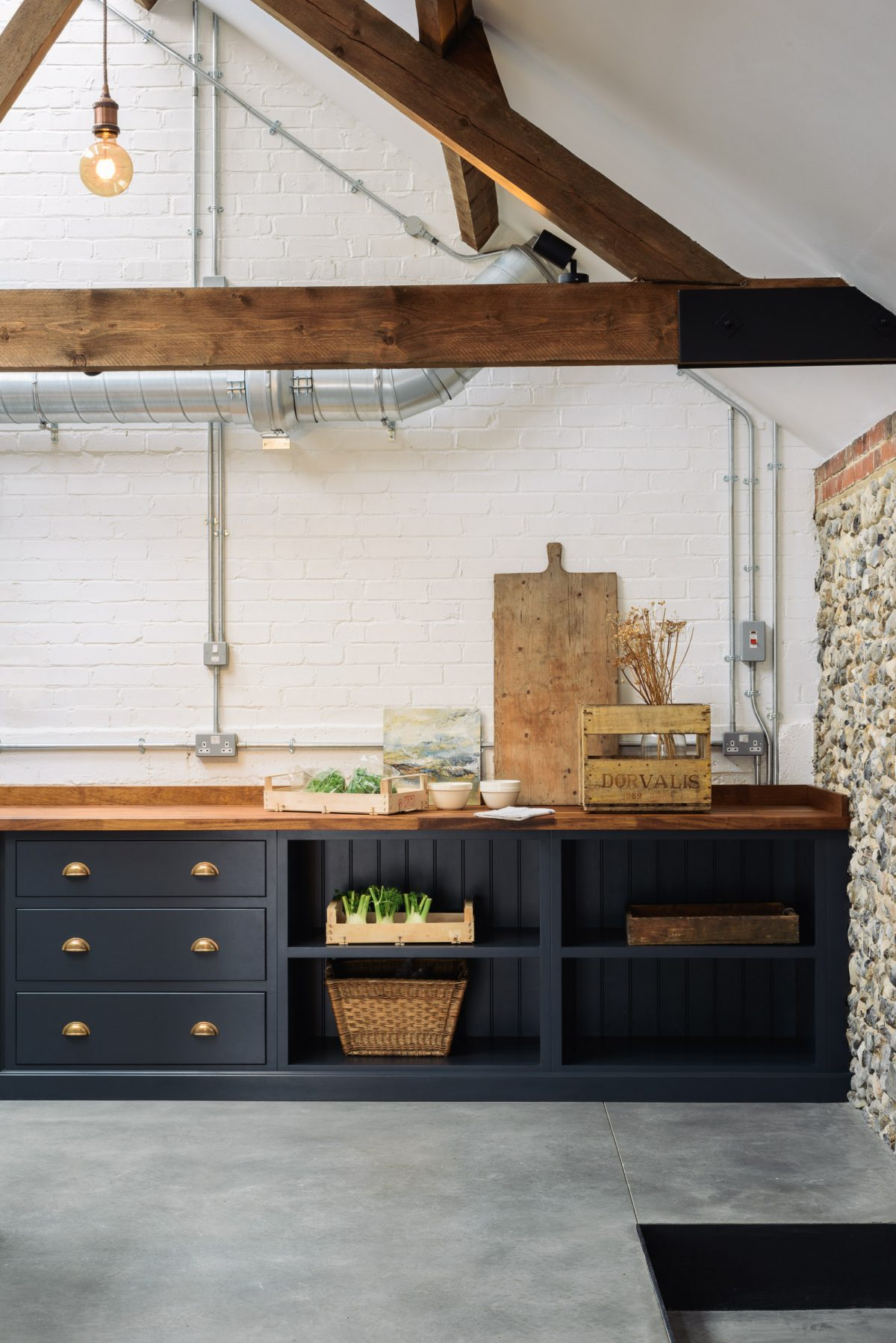 Polished concrete floors are beautifully softened by warm iroko worktops and original wooden beams.