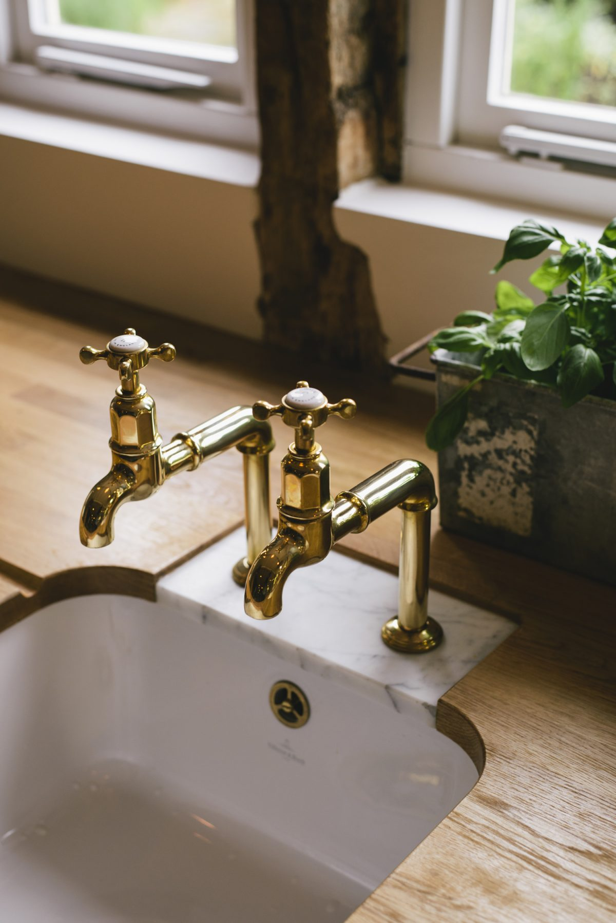 A pair of Aged Brass Mayan Taps set into a Carrara marble insert to prevent water damage.