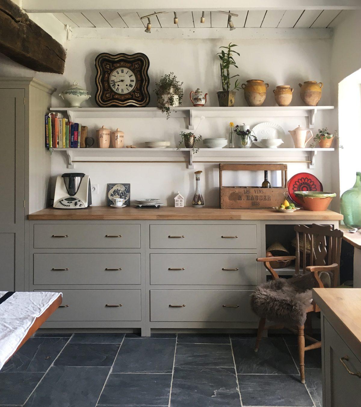 Mushroom cupboards, natural dark stone floors, wooden worktops and brass handles.